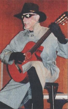 """Liedermacher Hans-Peter Lendle sitzt als der """"Gentechnik-Mann"""" mit Gitarre auf der Bühne"""