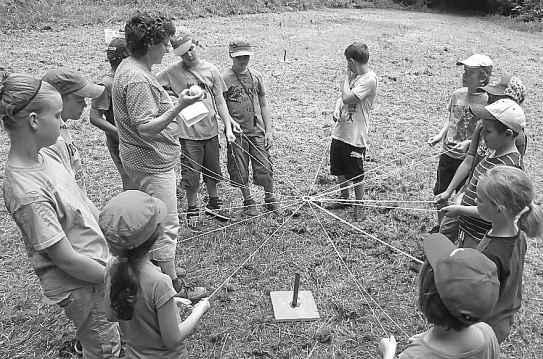 Ein Kreis von Kindern, die mit einer Art Fadenkreuz balancieren